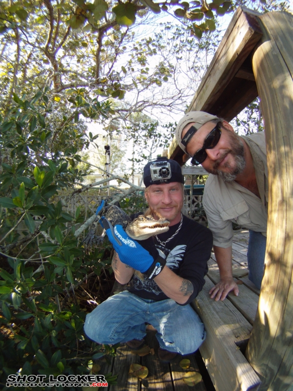 Brooks Paxton (left) and Sean PAxton (right) release a juvenile North American alligator they discovered gravely fouled on fishing gear.