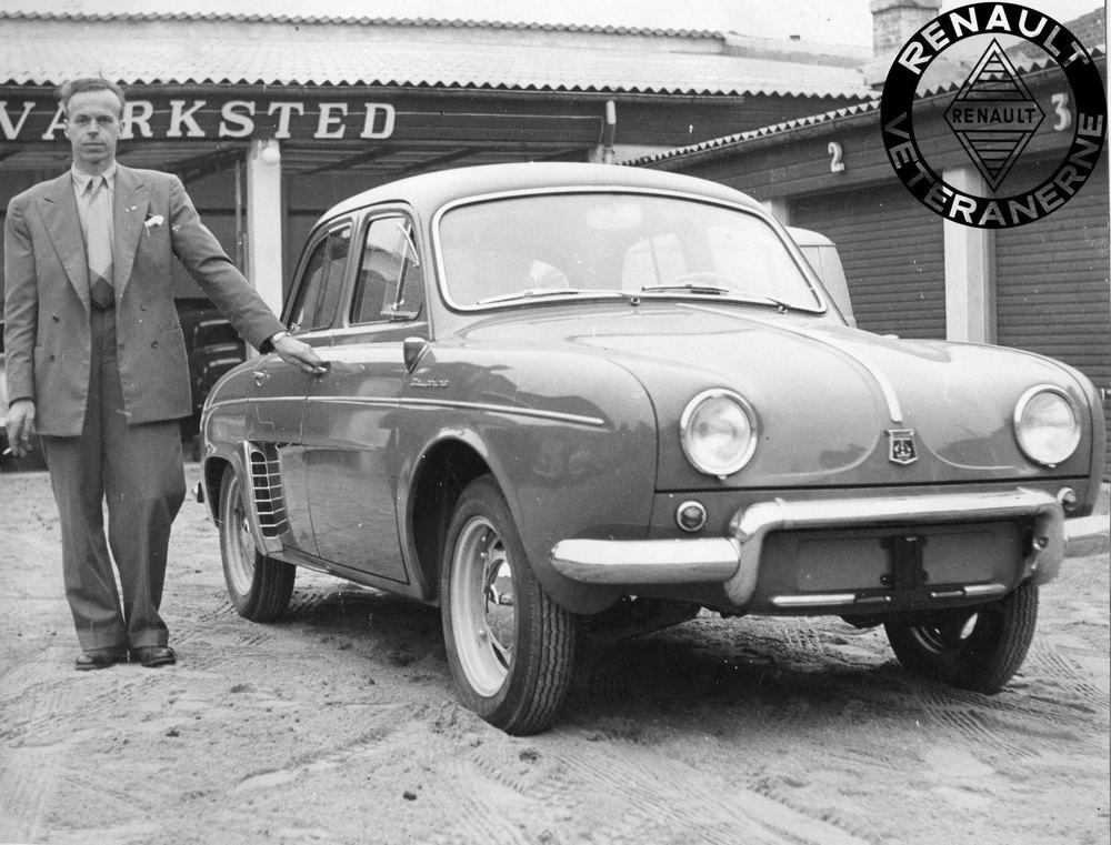 Alwyn Haugaard blev Renault-forhandler i Randers i foråret 1956 – netop som Dauphine blev lanceret. Den nye forhandler ses her med en af de allertidligste Dauphiner i Kronjylland. Bemærk, at bilen har stjernefælge ligesom 4CV, og de store sideblinklygter på forskærmen.