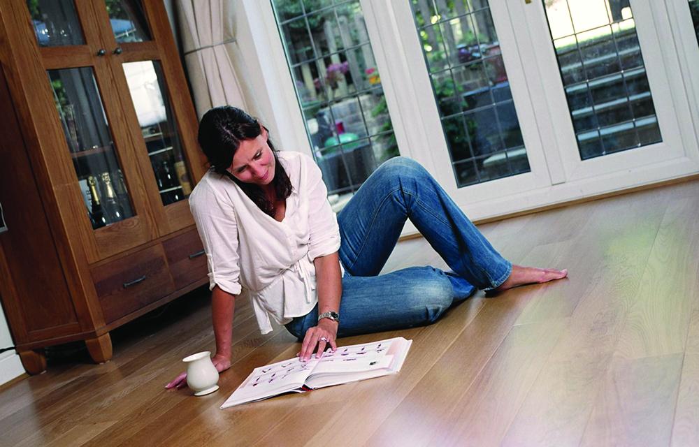woman reading on wooden floor