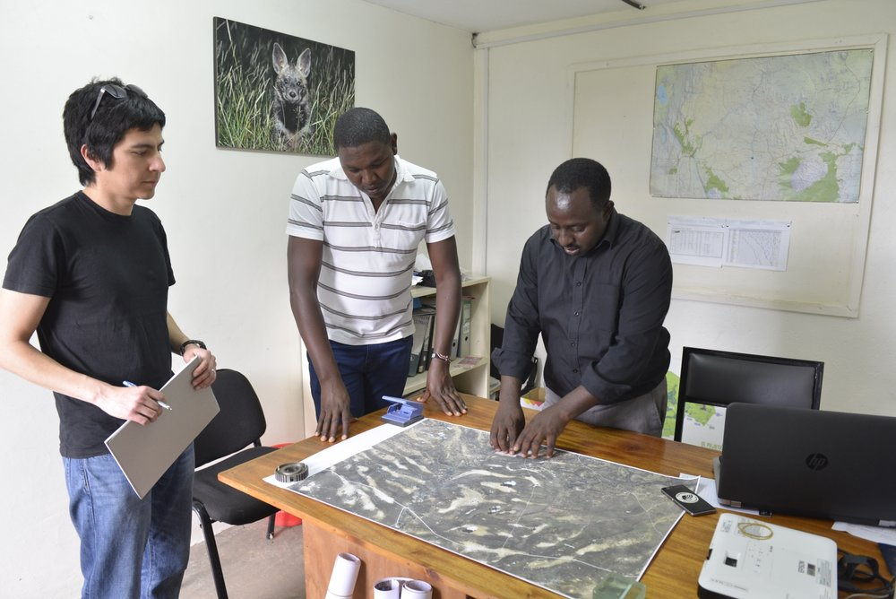 Bernard (centre) and Samuel (right) pointing out the different vegetation types at Ol Pejeta visible in the satellite image