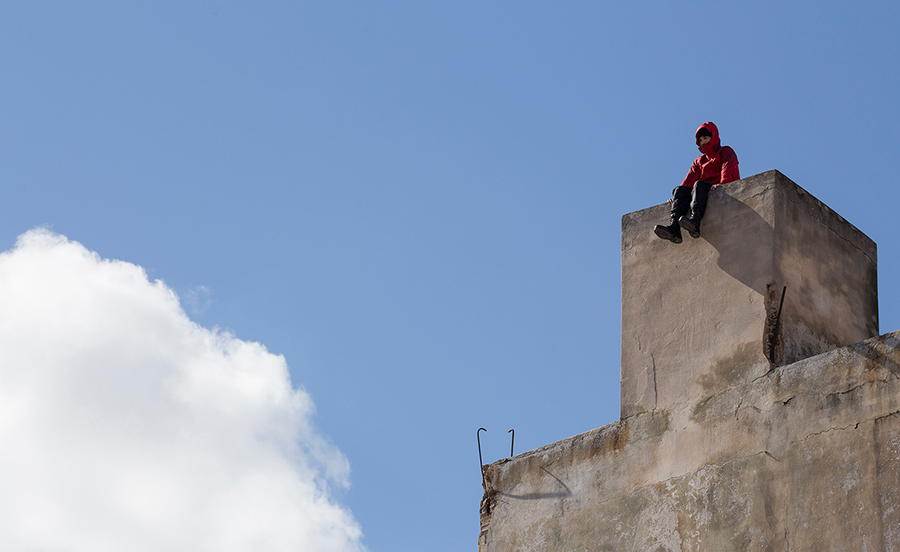 A PARTICIPANT ATTEMPTING TO CURE VERTIGO BY STANDING ON THE EDGE OF THE BUILDING. M.A. IS INTERESTED IN THE EFFECTS OF FEAR.