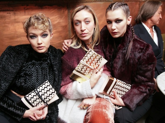 Gigi Hadid, Bella Hadid and Alana Hadid with the gold foil wrap clutch bag crafted by 5 Points and EB Leatherworks for Alana Hadid x Lou & Grey.