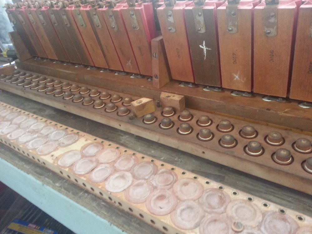 A dissembled player piano action showing from the top to the bottom: pneumatics, primary valves, and the leather pouches that activate them.  Note the hole in the pouch at the bottom center of the photo.