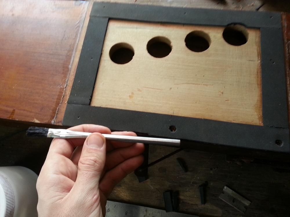 Cutting out the screw holes with the back end of a brush.