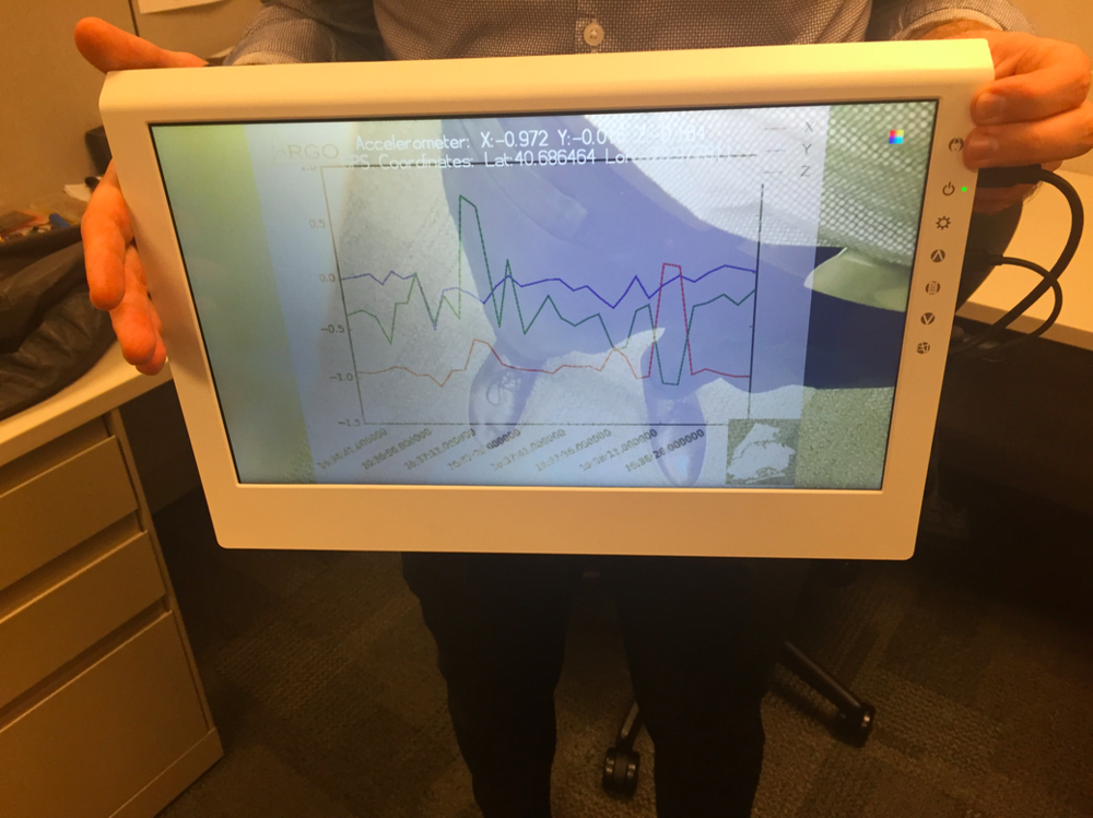 The LCD screen displaying a live video feed overlaid with a graph of accelerometer readings and annotations
