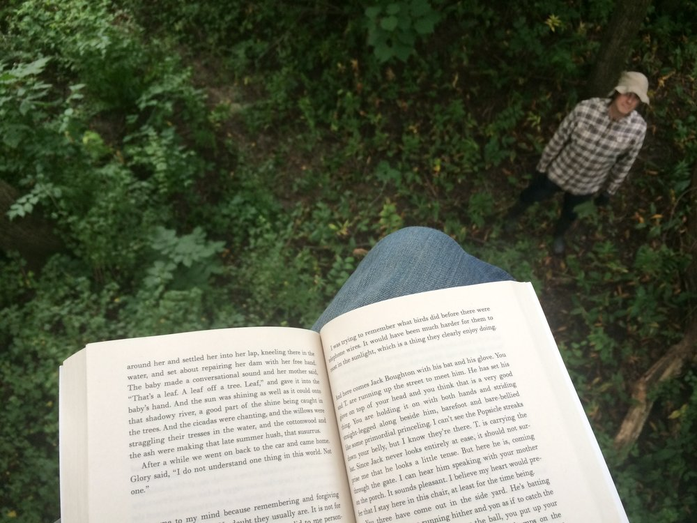 "Today I'm taking the summer reading outside--up the tree stand, to be precise. Josh moved the pigs into a glorious new silvopasture section, and we celebrated with a summer trek in  the basswoods. The mosquitoes are so bad we're even wearing GLOVES. We can't help it--the woods are so great.  The book?  Marilynne Robinson's  Gilead,  a lovely, powerful  CoreBook  read for  Wheaton College .   ""That's a leaf. A leaf off a tree."""
