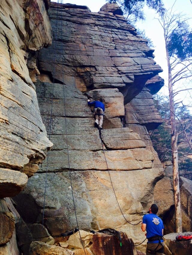 Plugging gear on the warmup route at the local crag.