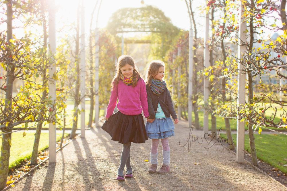 girls holding hand in back lit garden well dressed