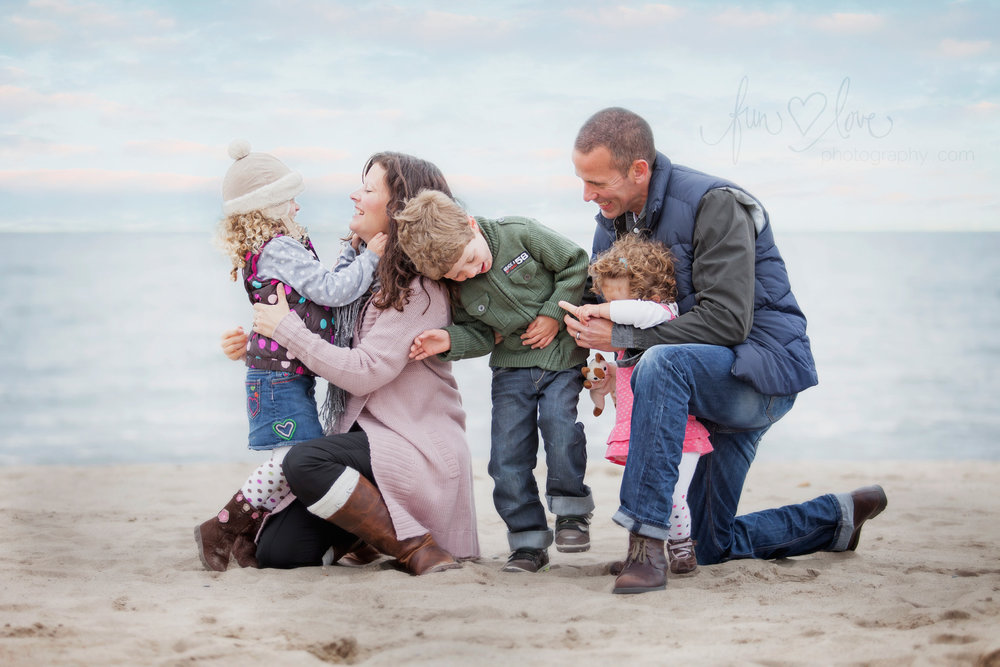 family dressed for autumn on the beach