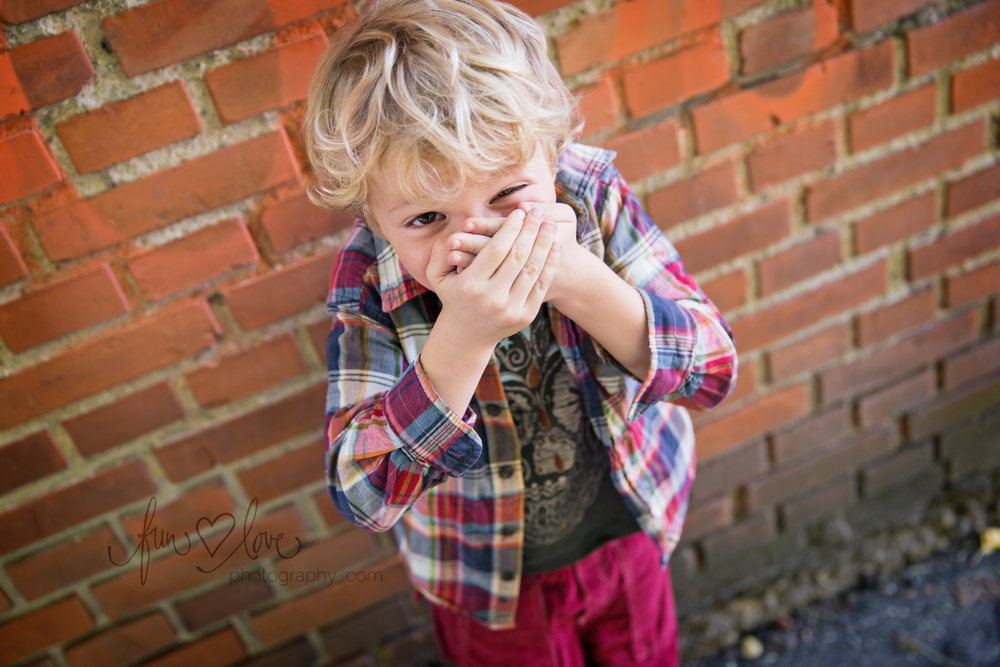 boy in plaid shirt against brick wall laughing covering mouth