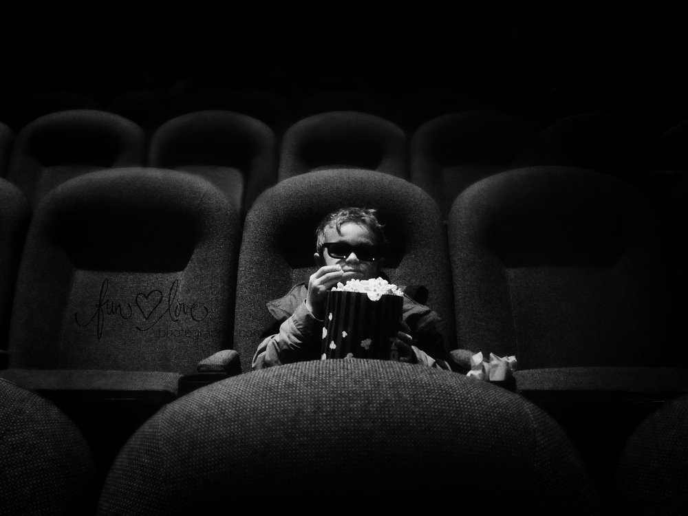 boy at a 3-D movie eating popcorn