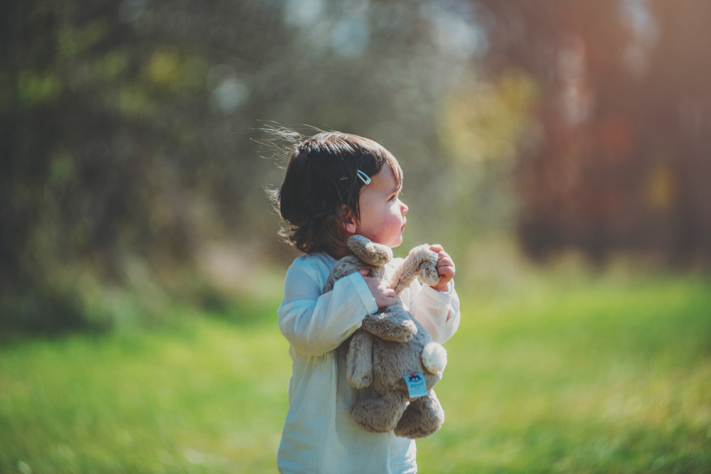 Toddler girl holds toy rabbit in sunshine Essex Documentary Portrait Photographer