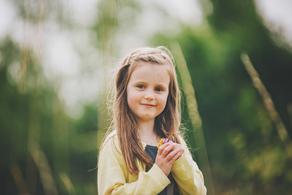 Little girl in long grass holds flowers Essex Documentary and Lifestyle Portrait Photographer