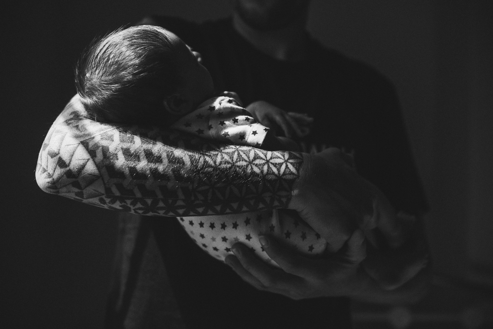 Tattoo'd Dad holds newborn son Essex Documentary and Lifestyle Portrait Photographer