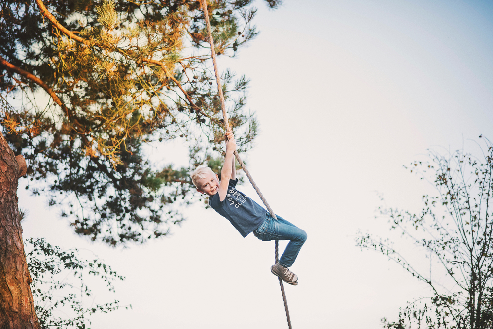 Young boy on rope swing Essex Documentary and Lifestyle Portrait Photographer
