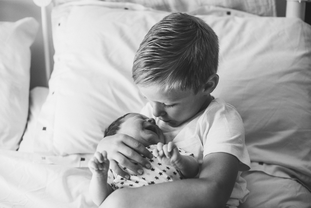 Little boy holds new baby brother Essex Documentary and Lifestyle Portrait Photographer