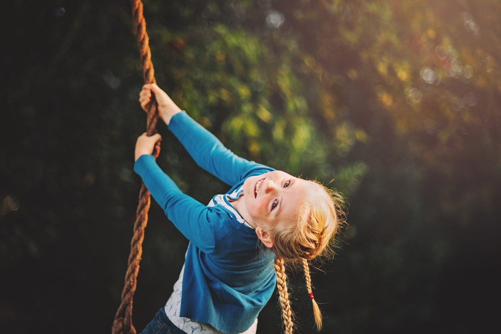 Young girl hangs on a rope swing Essex Documentary and Lifestyle Portrait Photographer
