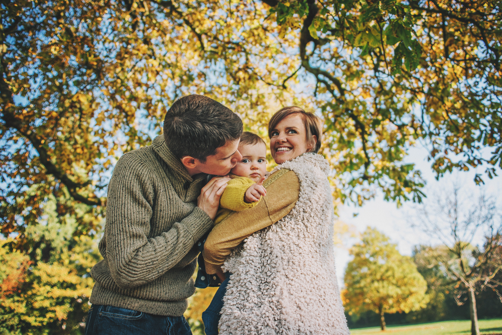Parents with baby girl under Autumn tree Essex Documentary and Lifestyle Portrait Photographer