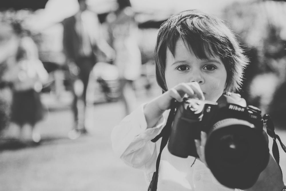 Young boy with big camera Hylands House Essex UK Documentary Wedding Photographer