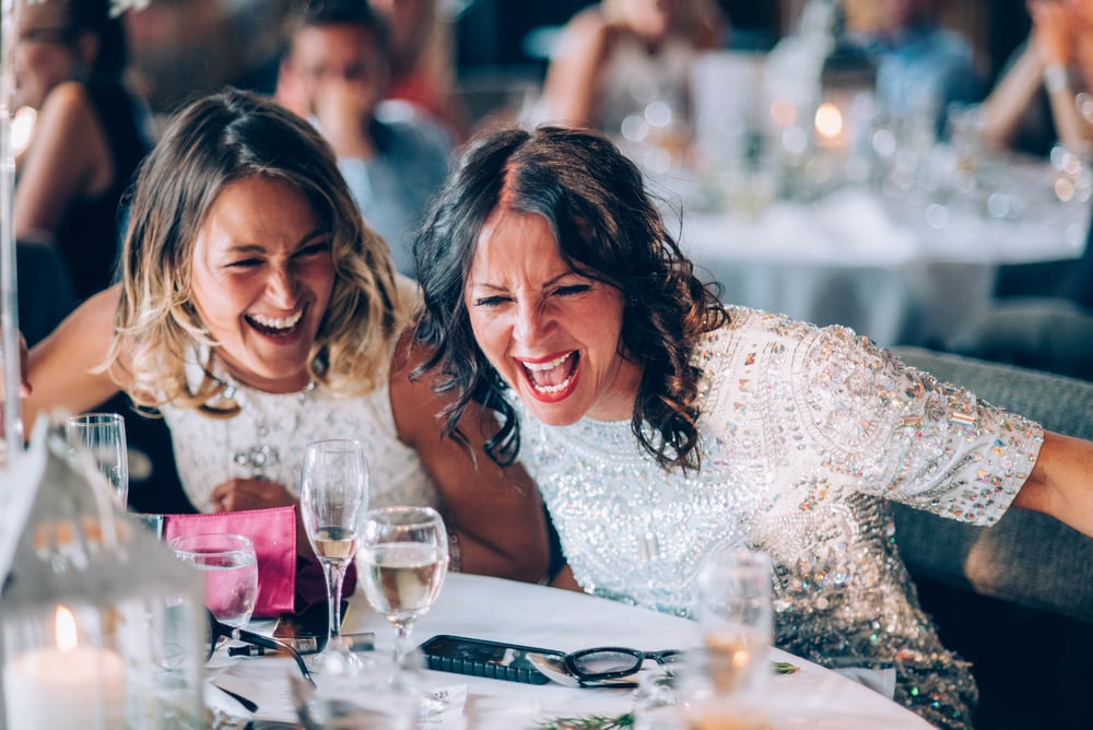 Two guests laugh in London Pub Wedding Essex UK Documentary Wedding Photographer