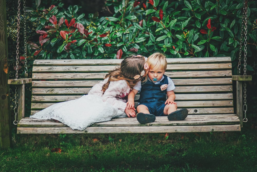 Flower girl kisses boy on bench Rustic Essex UK Documentary Wedding Photographer