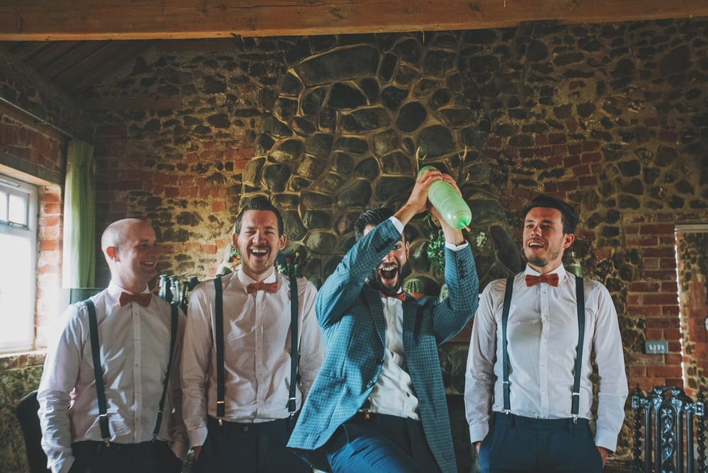 Groom in braces bow tie catches balloon Cliff Barns Norfolk Essex UK Documentary Wedding Photographer