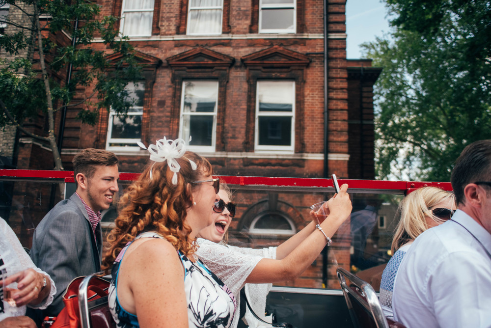 Guests take selfies on London Bus Essex UK Documentary Wedding Photographer