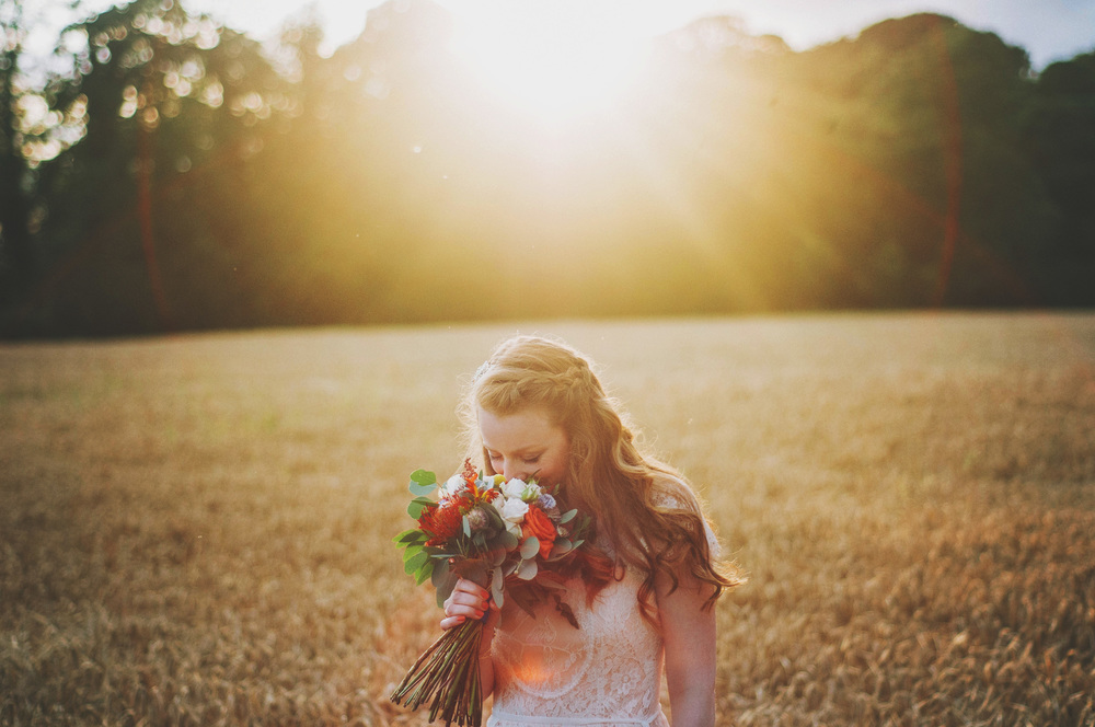 bride smells bouquet sunset cornfield Cliff Barns Norfolk Essex UK Documentary Wedding Photographer