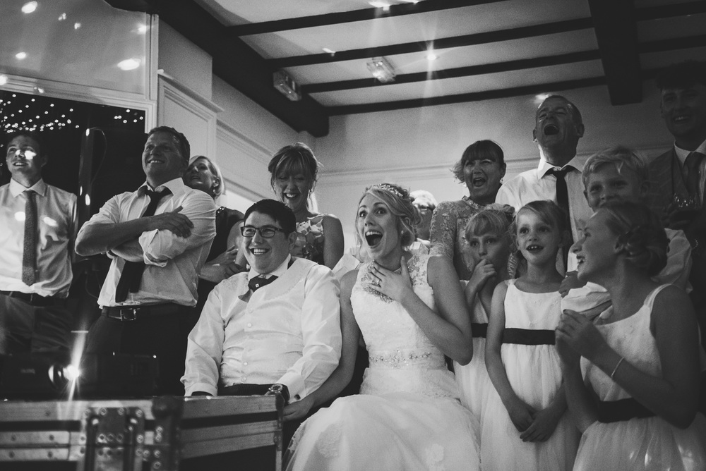 Bride and Groom watch funny speech video Wood Hall Suffolk Essex UK Documentary Wedding Photographer