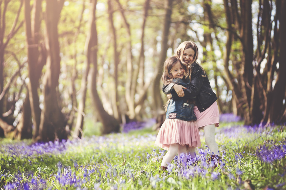 Two sisters hug in Bluebell Wood Essex UK Documentary Portrait and Lifestyle Photographer