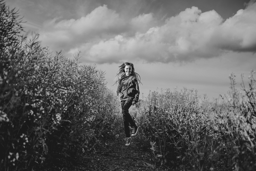 Tween girl jumps in field cloudy sky Essex UK Documentary Portrait and Lifestyle Photographer