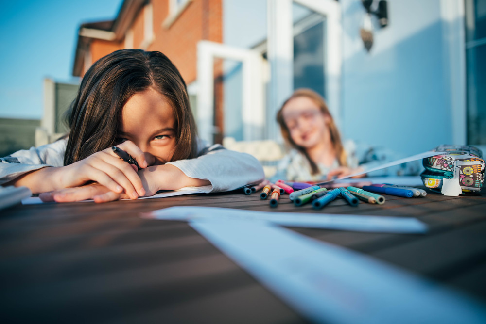 Two girls draw at outside table Essex UK Documentary Portrait and Lifestyle Photographer