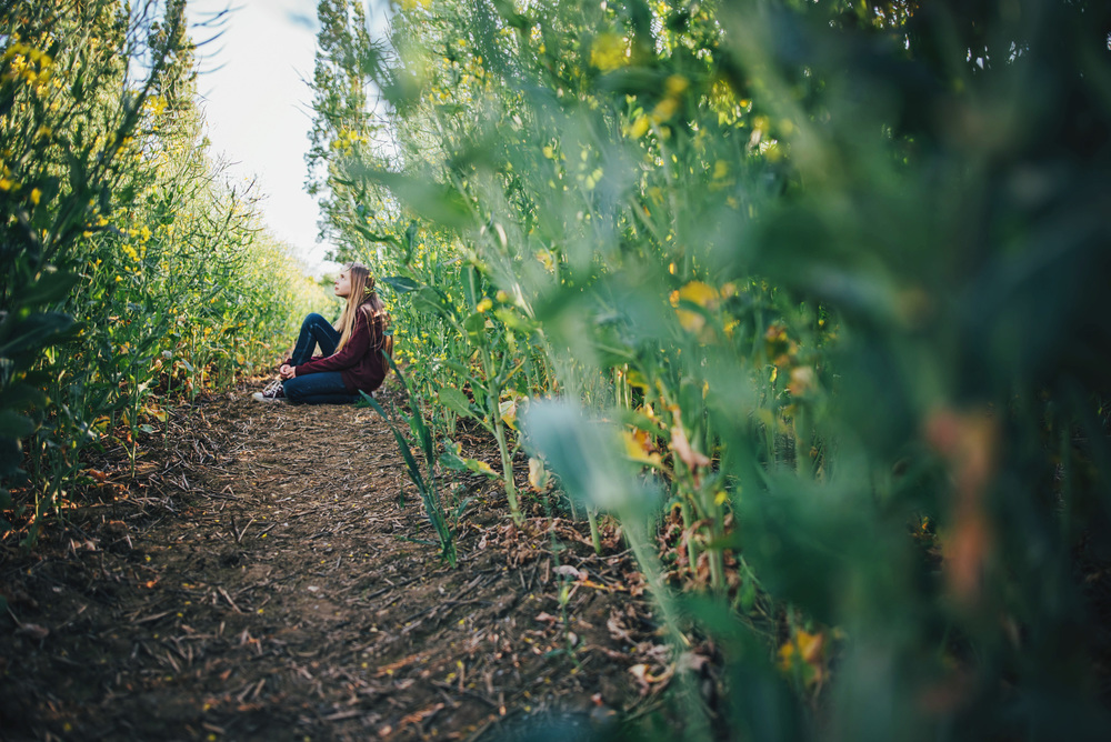 Tween girl sits in green field Essex UK Documentary Portrait and Lifestyle Photographer