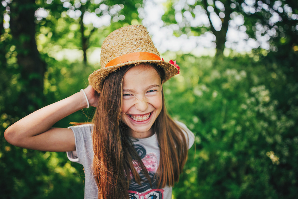 Girl in sunhat laughs in field Essex UK Documentary Portrait and Lifestyle Photographer