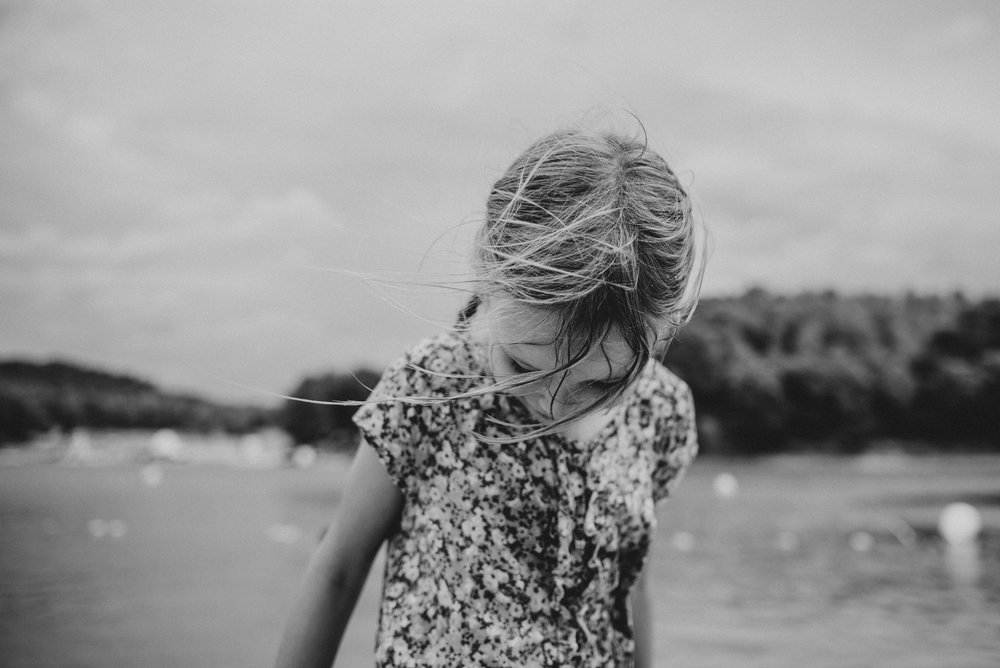 Young girl looks down as she walks out of a lake Essex UK Documentary Portrait Photographer
