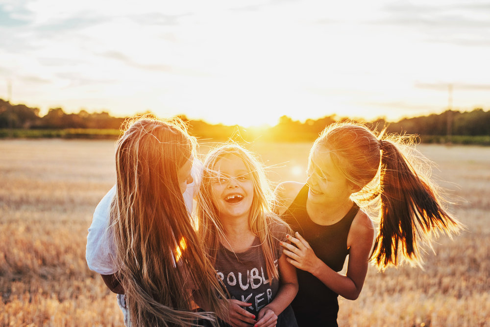 Three girls stand in cornfield laughing at sunset Essex UK Documentary Portrait Photographer
