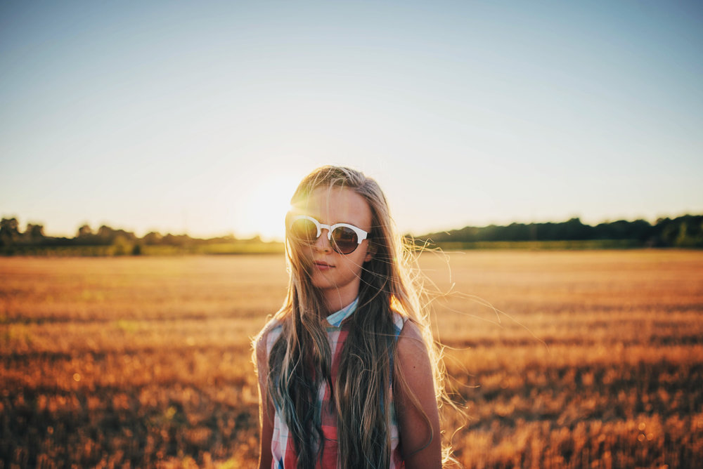 Young girl in sunglasses in cornfield at sunset Essex UK Documentary Portrait Photographer