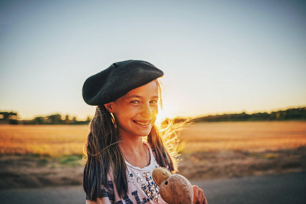 Young girl in beret stands in cornfield at sunset Essex UK Documentary Portrait photographer