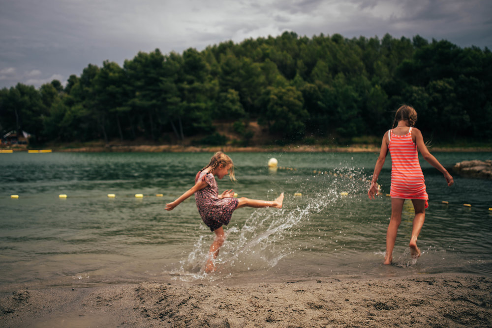 Young girl kicks water at sister in Lake Essex UK Documentary Portrait Photographer