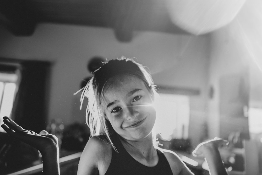 Girl dances in kitchen with sun flare Essex UK Documentary Portrait Photographer