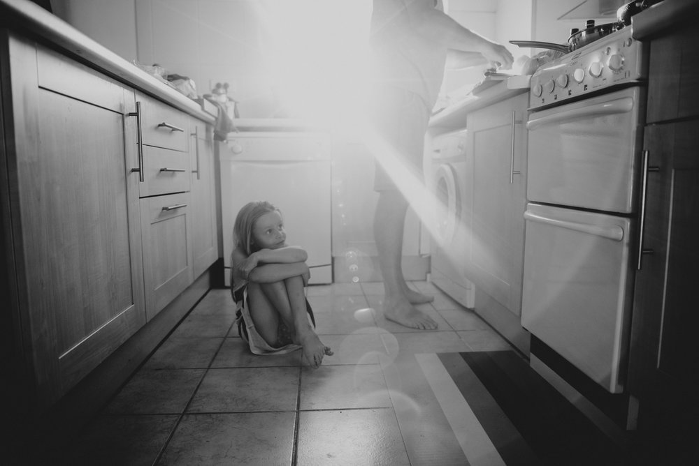 Young girl sits on kitchen floor with sun flare Essex UK Documentary Portrait Photographer