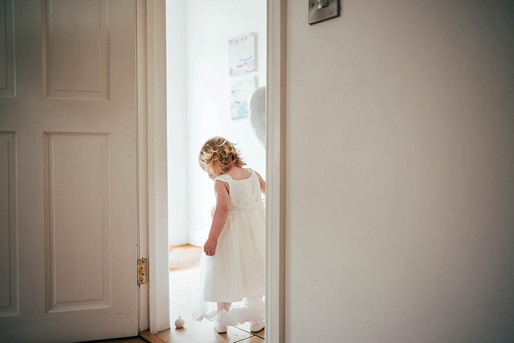 Bride Groom Essex Wedding Photographer Documentary Blake Hall Bridesmaid in doorway with balloonw