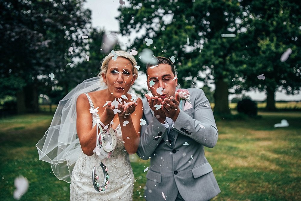 Bride Groom Essex Wedding Photographer Documentary Blake Hall Couple blow confetti