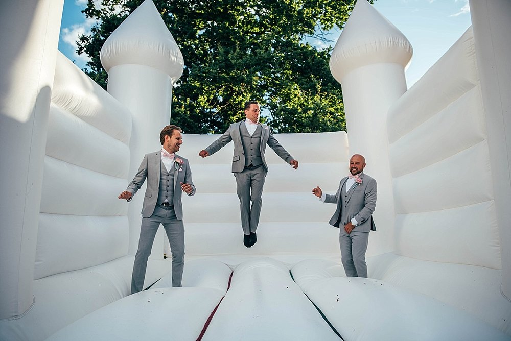 Bride Groom Essex Wedding Photographer Documentary Blake Hall Groom Groomsmen on Bouncy Castle