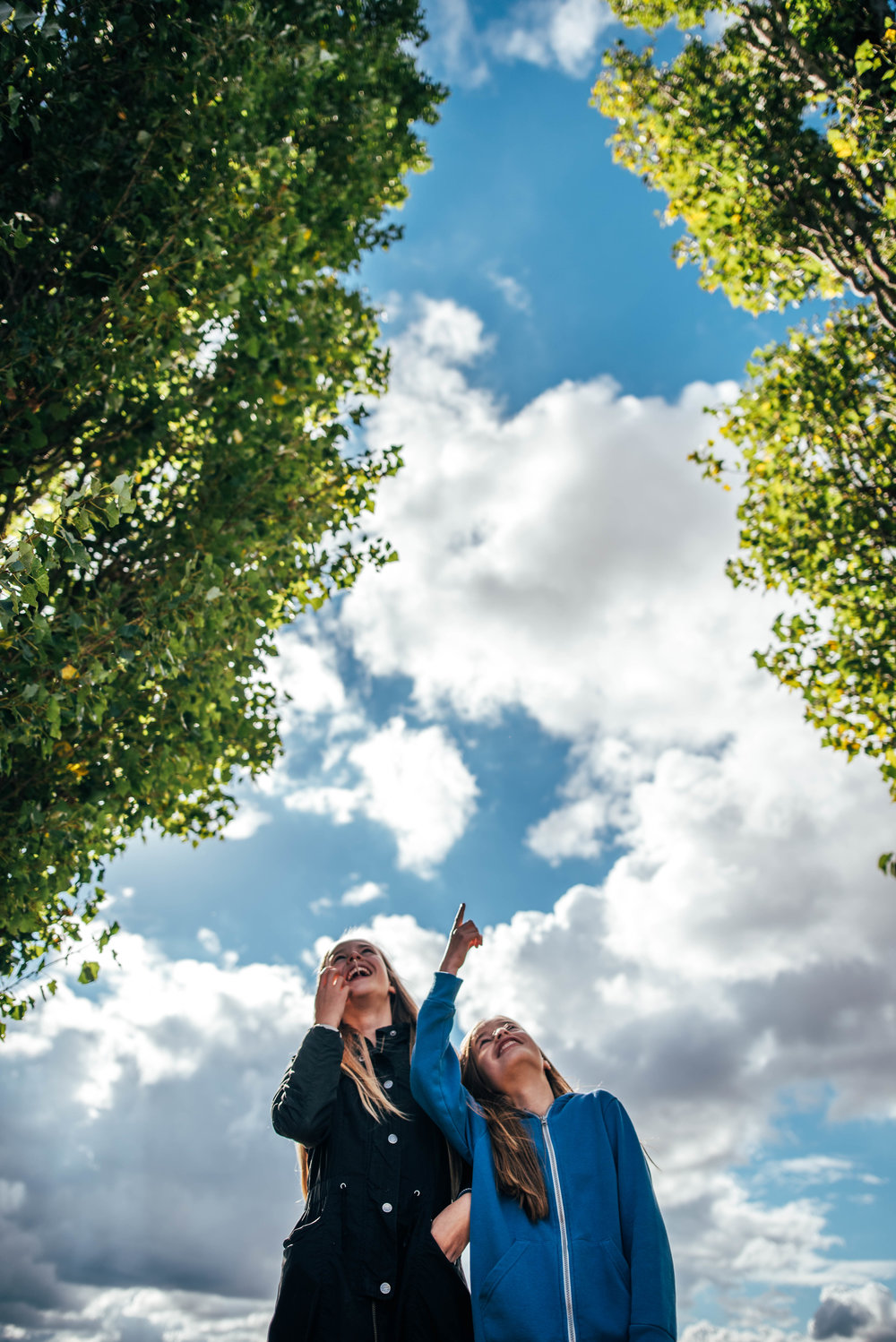 Two girls stand framed by trees against big cloudy sky Essex UK Documentary Portrait Photographer