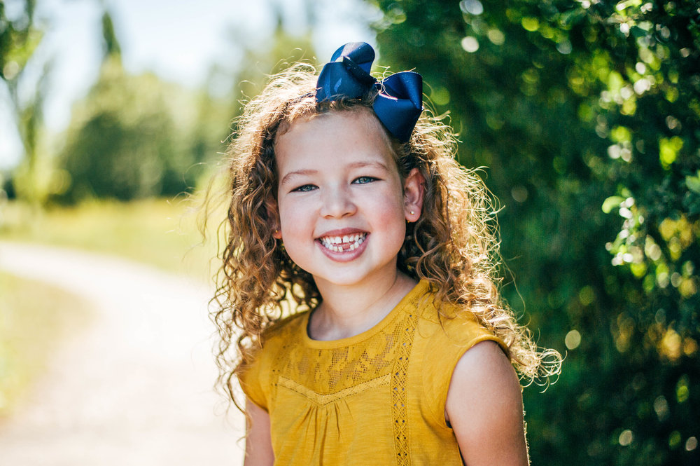 Little girl smiles on bridge Essex UK Natural Documentary Portrait Photographer