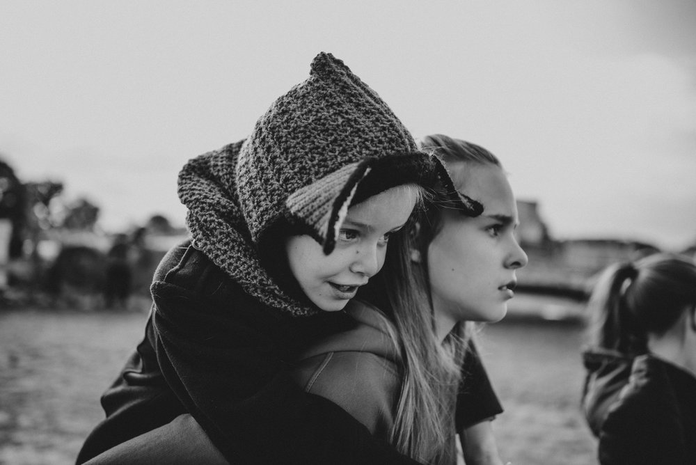 Little girl in Fox hat on sisters back Essex UK Documentary Portrait Photographer