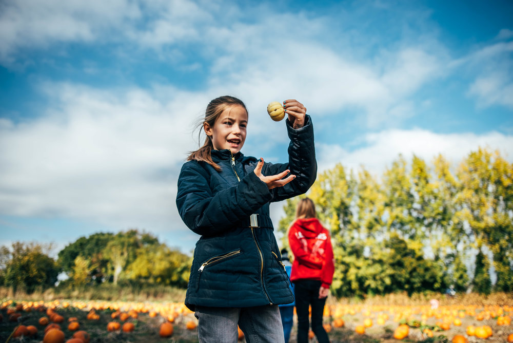 Young girl holds pumpkin up Essex UK Documentary Portrait Photographer