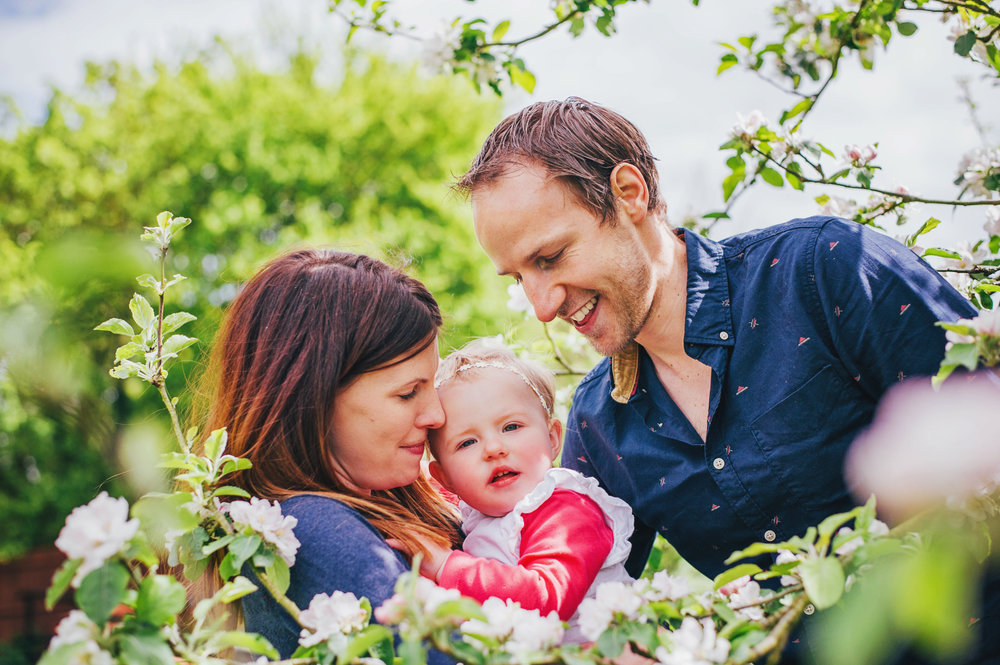 Mum and Dad with baby girl in Blossom At Home Lifestyle Shoot Essex UK Documentary Portrait Photographer