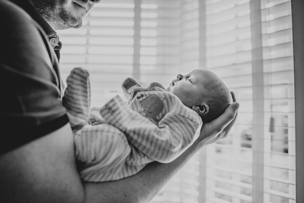 New Dad holds baby girl in windows light At Home Lifestyle Shoot Essex UK Documentary Portrait Photographer